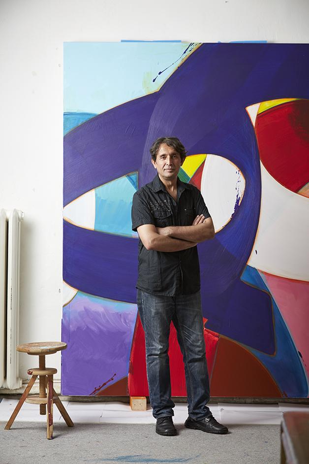 Der afghanisch-deutsche Künstler Aatifi in seinem Bielefelder Atelier vor einer abstrakt-skripturalen Malerei aus dem Jahr 2014. Foto: © Wolfgang Holm